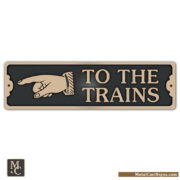 To The Trains bronze sign w/ left pointing hand